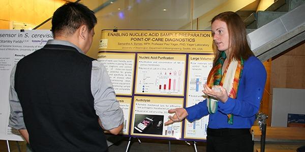 Students discussing research poster at UW Bioengineering BioEngage symposium
