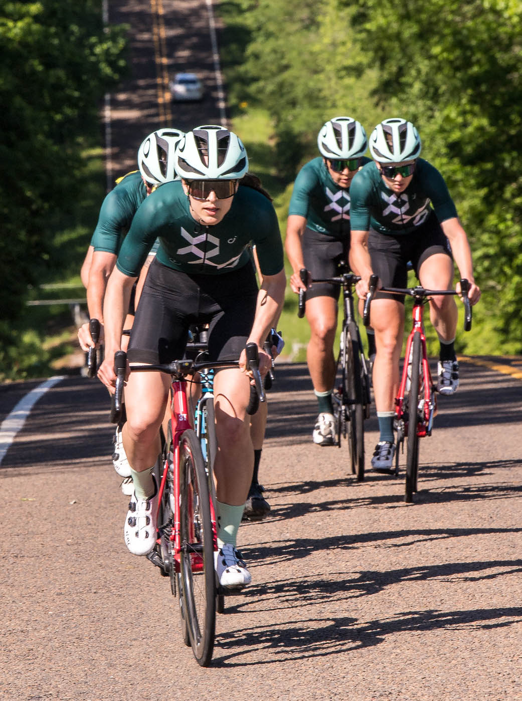 Kathleen Abadie and cycling team riding up hill