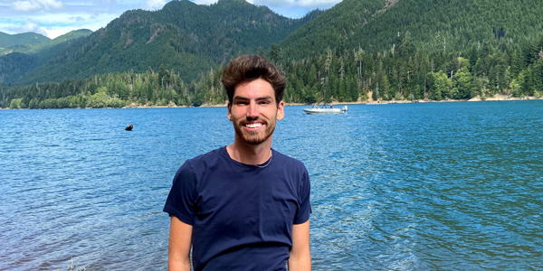 Jamison Siebart standing in front of lake with mountains in background