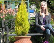 Dr. Alyssa Taylor sitting on a bench in a garden