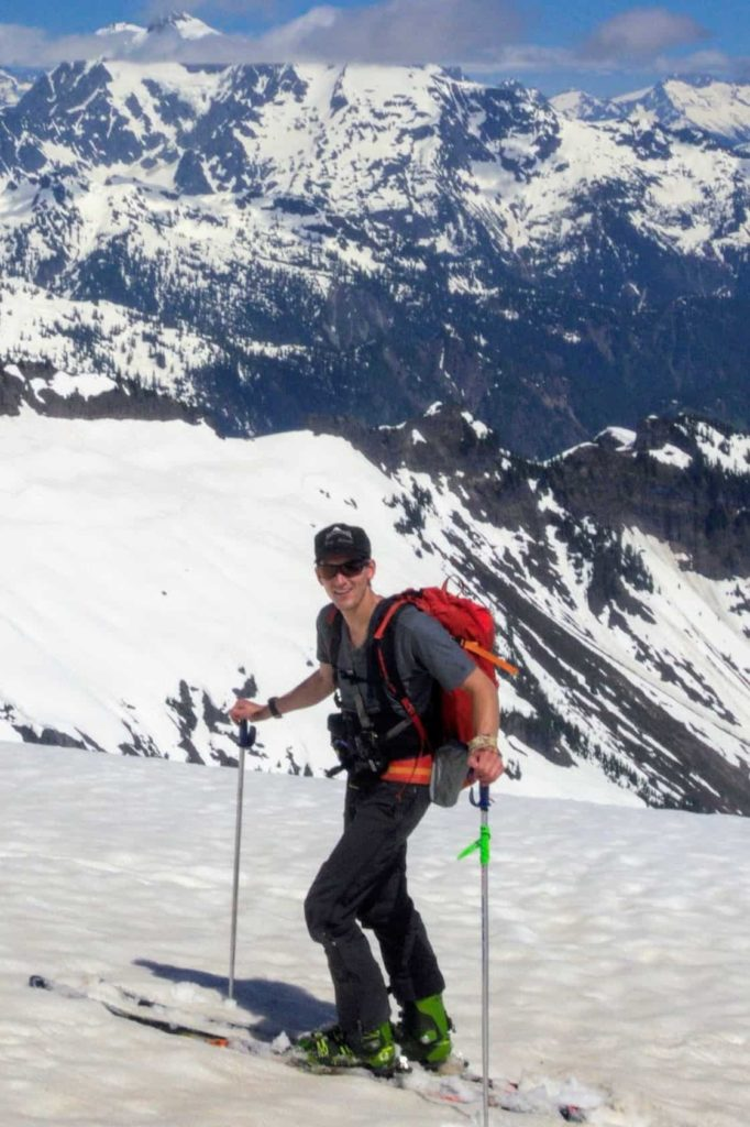 UW master's student Dylan Guelig on skis on mountaintop
