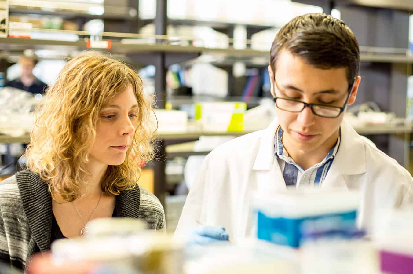 photo of Kelly Stevens and Daniel Corbett looking down at lab bench.