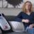 Woman sitting on sofa with portable kidney dialysis prototype next to her